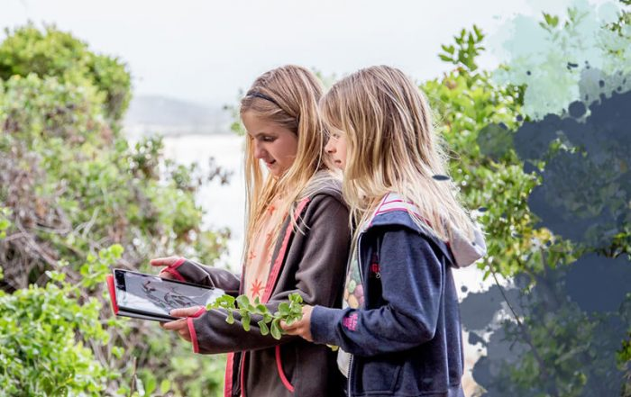Two girls searching looking at a tablet out in the forest.